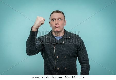 Enraged Nervous Man Threatens Someone With His Fist And Is Making An Admonition Isolated On Blue Bac