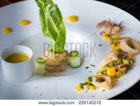 Calamari With Mango Sauce With Nice Decoration On White Plate.