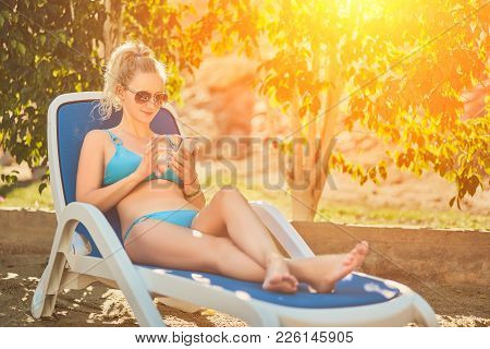 Young Woman Relaxing On Deck Chair. Girl In Bikini Lying Near Swimming Pool. Woman Sunbathing In Bik