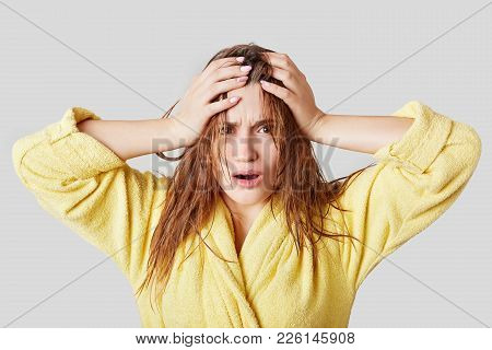 Frustrated Female Touches Head, Has Wet Hair And Disorder, Doesn`t Know What To Wear And Which Hairs