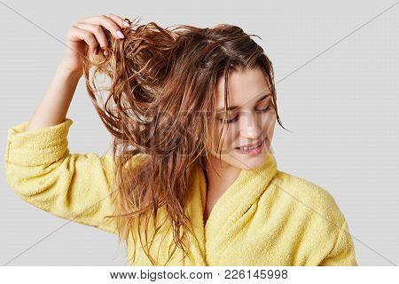 Close Up Shot Of Pleased Female Demonstartes Her Long Cared Natural Hair Wet After Taking Shower, Be