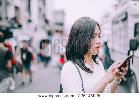 Side View Of A Young Woman Playing Mobile Phone On The Famous Backpacker Street Khao San In Bangkok,