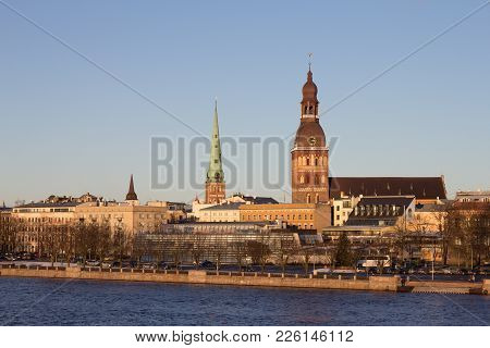 Riga, Latvia. The View Of 11 November Embankment Of River Daugava. The Towers, Steeples Of Riga Cath