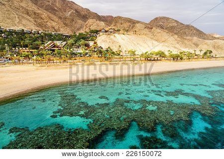 Coral Reef Of Aqaba Bay In Red Sea, Empty Beach And Desert Near Eilat, Israel. Contrast Between Turq