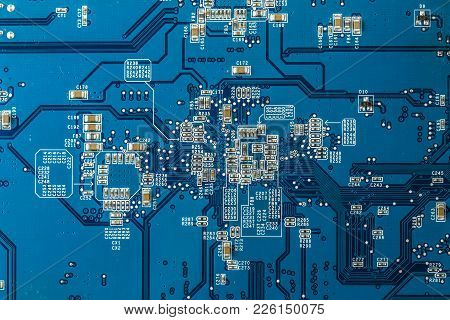 Close Up Photo Of Blue Printecd Circuit Board With Electronic Parts
