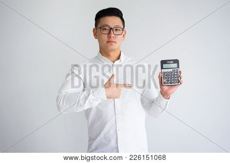 Confident Asian Man Showing Calculator And Pointing At Empty Screen. Young Book Keeper Presenting Pr