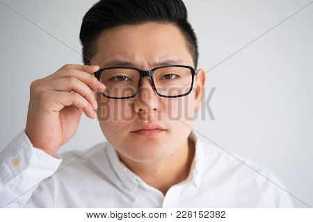 Focused Asian Man Touching Temple And Peering Through Glasses. Student Suffering From Weak Sight. Ba