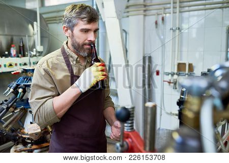 Pensive Dreamy Brewing Engineer Wearing Apron And Gloves Smelling Beer While Holding Open Bottle Nea