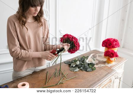 Smiling Lovely Young Woman Florist Arranging Plants In Flower Shop. People, Business, Sale And Flori