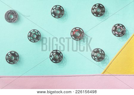 Collage Of Metal Bobbin Spools On Seamed Fabrics In Pastel Tones - Trendy Decoration With Flat Shado