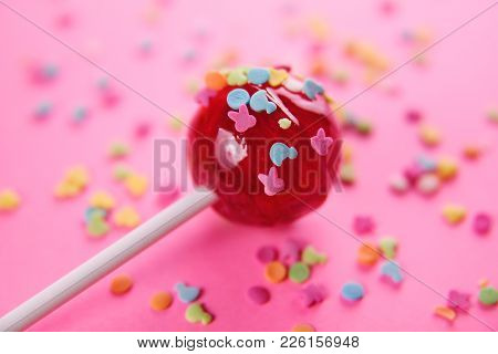 Pink Round Lollipop Close-up On Pink Background. Color Glaze In The Form Of Small Animal Figures Is