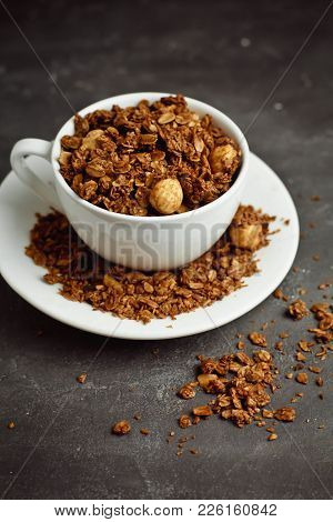 Granola In A White Cup On A Black Background. The Concept Of A Healthy Diet, Weight Loss, Diet