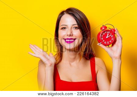 Young Girl In Red Dress With Redalarm Clock
