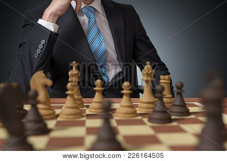 Young Man Is Thinking And Playing Chess.