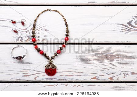 Ladies Necklace From Colored Stones. Women Necklace, Bracelet And Rings Made From Red Stones On Whit