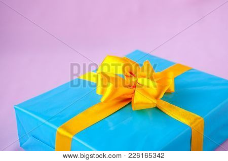 Gift In A Blue Box With An Yellow Bow On A Pink Background