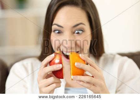 Woman Joining Half An Apple And Orange Sitting On A Couch In The Living Room At Home
