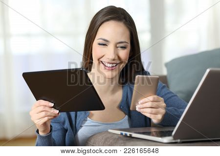 Happy Woman Using Multiple Devices On A Couch In The Living Room At Home