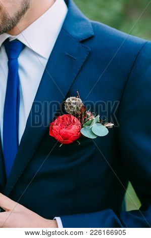 Close Up Image Of A Groom In A Blue Tuxedo With Red Boutonniere. Boutonniere On The Groom's Jacket.