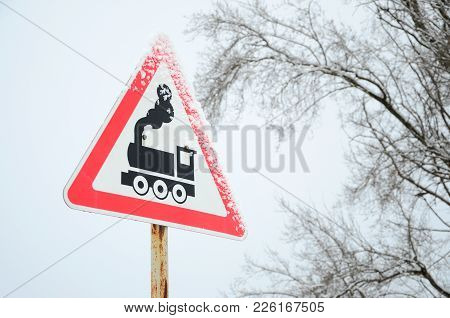 Railway Crossing Without Barrier. A Road Sign Depicting An Old Black Locomotive, Located In A Red Tr