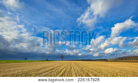 Stubble Field Landscape Under Cloudy Sky. Beautiful Polish Landscape.