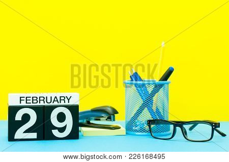 February 29th. Day 29 Of February Month, Calendar On Yellow Background With Office Supplies. Winter