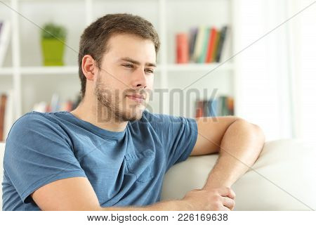Serious Man Thinking Looking Away Sitting On A Couch In The Living Room At Home