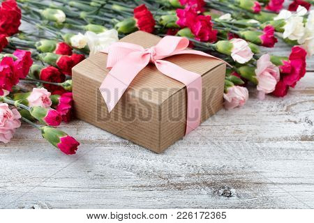 Gift Box With Colorful Carnations In Background On White Weathered Wooden Boards
