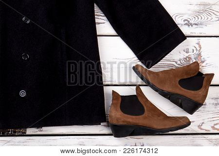 Close Up Women Coat And Boots. Female Short Coat And Stylish Brown Shoes, Vintage Wooden Background.