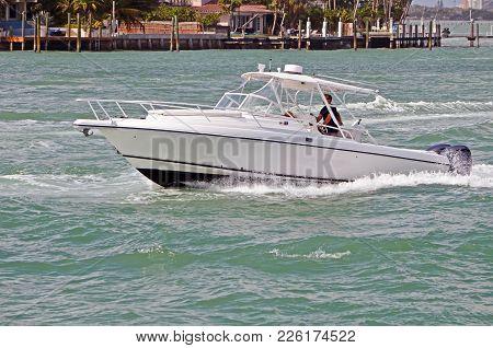 White Sport Fishing Boat Cruising Off Rivaalta An Upscale Island Community In Miami Beach,florida