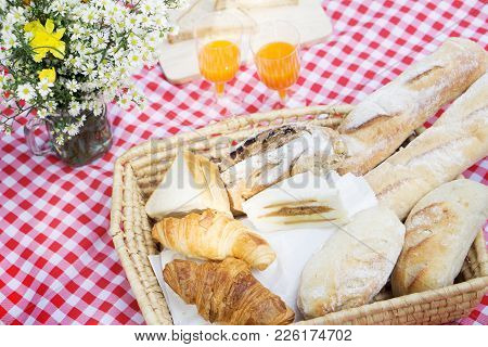 Picnic Lunch Meal Outdoors Park Food Concept, Closeup Of Picnic Basket With Drinks, Food And Flowers