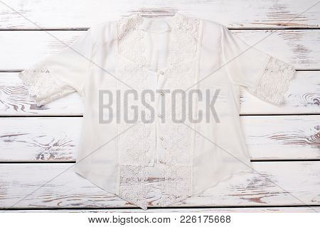 Female White Silk Blouse With Lace. Beautiful Woman Shirt With Short Sleeves On White Wooden Table.