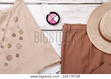 Set Of Female Clothes On Wooden Background. Women Straw Hat, Trousers And Blouse. Feminine Clothing