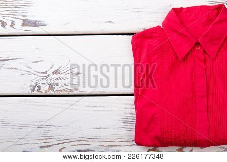 Female Elegant Shirt And Copy Space. Women Red Blouse Folded On Wooden Background. Fashion Design Cl