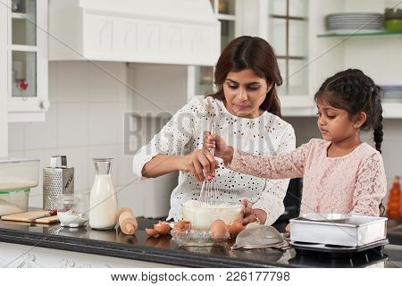 Attractive Middle-aged Woman And Her Cute Little Daughter Beating Eggs And Flour With Whisk While Ma