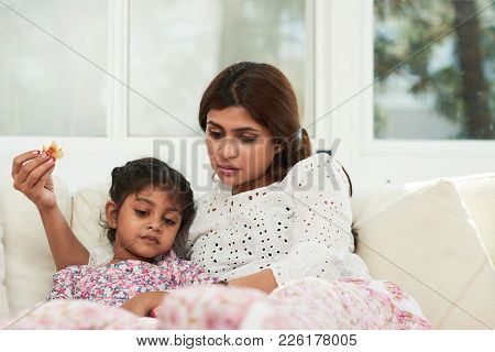 Spending Lazy Weekend At Home: Pretty Indian Woman And Her Cute Little Daughter Lying On Cozy Sofa,