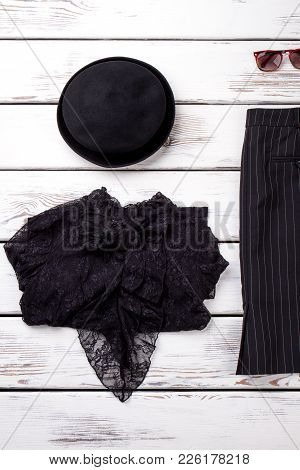 Set Of Female Black Clothes, Wooden Background. Women Black Vintage Hat, Lace Blouse And Skirt. Femi