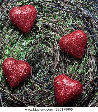 Four Red Shiny Hearts On A Green Mossy Background