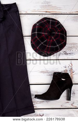 Women Black Trousers And Boots. Female Black Ankle Boots And Cap On White Wooden Background. Feminin