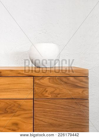 Simple White Ceramic Vase Decorating A Wooden Chest Of Drawers.
