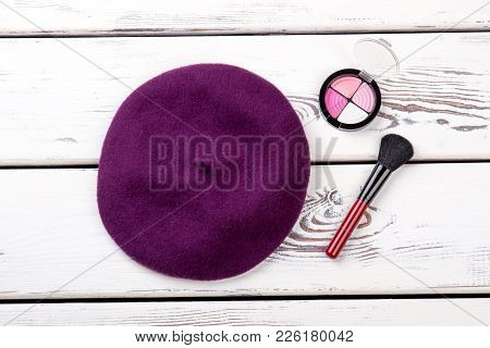 Female French Beret And Cosmetics. Women Autumn Hat, Eyeshadows And Brush On White Wooden Background