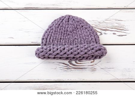 Female Merino Knitted Hat. Women Purple Color Winter Hat On White Wooden Background. Ladies Winter F