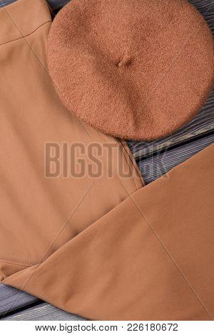 Set Of Female Elegant Garment. Women Brown Trousers And Beret On Wooden Background. Feminine Stylish