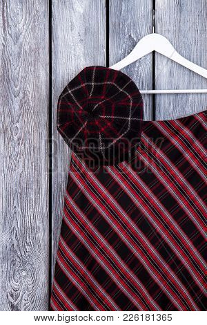 Female Elegant Clothes, Wooden Background. Women Warm Cap And Skirt Hanging On Hanger. Clothes At Ho