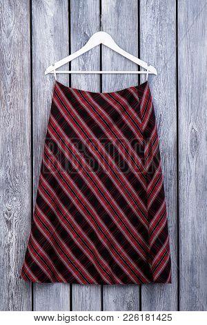 Women Skirt Hanging On Hanger. Female Classy Apparel On Old Wooden Background. Feminine Outlet On Sa