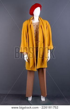 Mannequin Dressed In Yellow Elegant Topcoat. Fashion Autumn Outfit On Female Mannequin, Grey Backgro