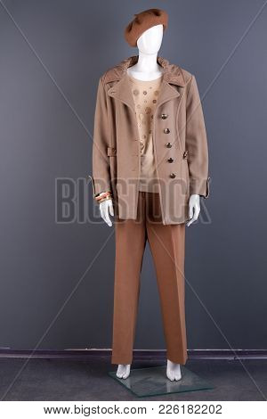 Women Stylish Beige Top Coat On Mannequin. Female Mannequin Dressed In Classy Brown Beret And Trouse