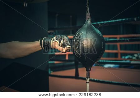 Active Man In A Gloves Beats A Punching Bag In A Gym Close Up.