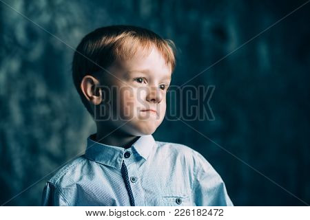 Five year old boy is standing with a puzzled expression. Childhood. Kid's fashion.