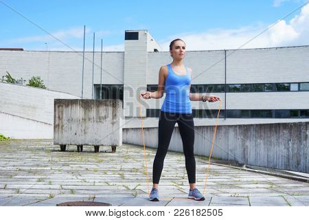 Young, fit and sporty woman jumping with a skipping rope. Fitness, sport, urban jogging and healthy lifestyle concept.